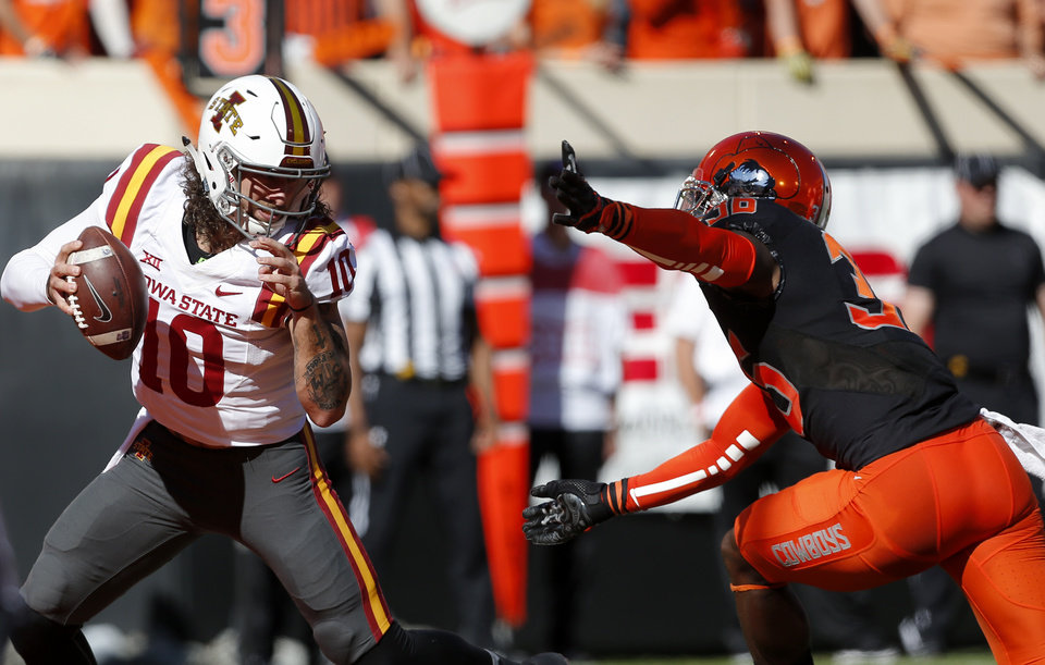 Photo - Iowa State's Jacob Park (10) gets by Oklahoma State's Derrick Moncrief (36) during a college football game between the Oklahoma State University Cowboys (OSU) and the Iowa State University at Boone Pickens Stadium in Stillwater, Okla., Saturday, Oct. 8, 2016. Photo by Sarah Phipps, The Oklahoman