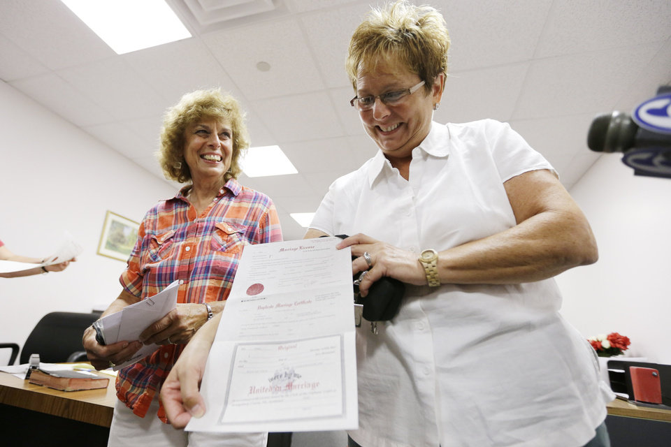 Ellen Toplin, right, and Charlene Kurland pose for photographs with their marriage license at a Montgomery County office despite a state law banning such unions, Wednesday, July 24, 2013, in Norristown, Pa.  The chairman of the Montgomery County commissioners, Democrat Josh Shapiro, said he supports same-sex marriage and was ready for the county to defend the stance in court.   (AP Photo/Matt Rourke)