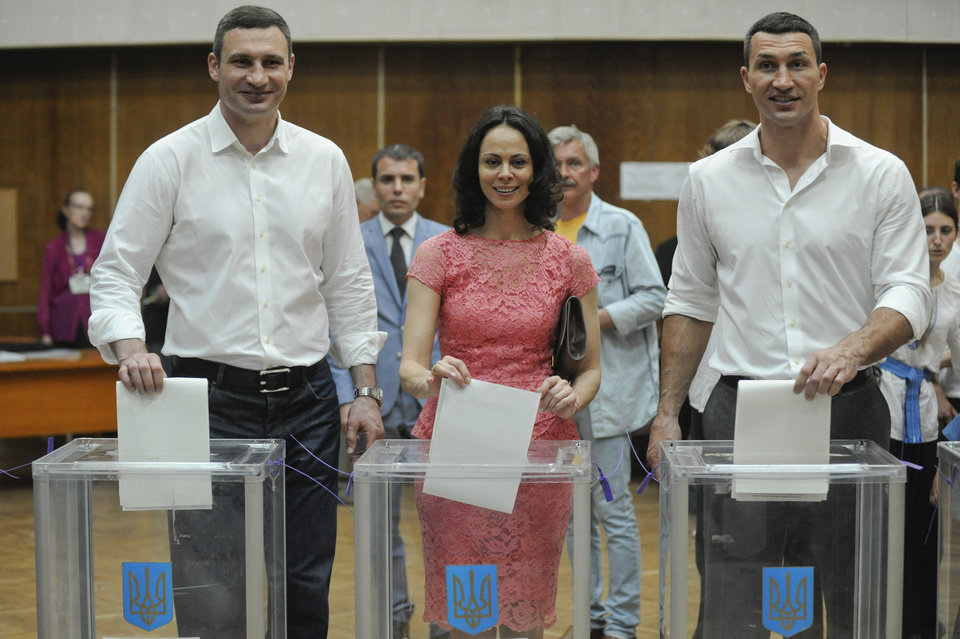 Photo - Vitali Klitschko, left, Kiev's mayoral candidate, his wife Natalia, center, and his brother boxer Wladimir Klitschko cast their ballots at a polling station during presidential and mayoral elections in Kiev, Ukraine, Sunday, May 25, 2014. Ukraine's critical presidential election got underway Sunday under the wary scrutiny of a world eager for stability in a country rocked by a deadly uprising in the east. (AP Photo/Evgeniy Maloletka)