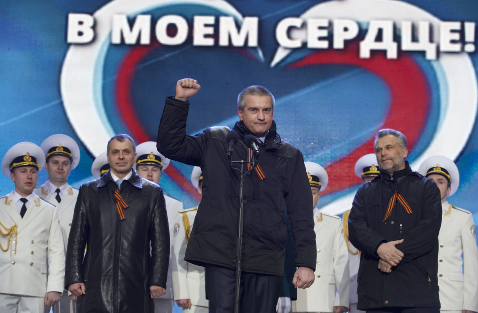 Photo - Crimean leaders, from left, Speaker of Crimean legislature Vladimir Konstantinov, Crimean Premier Sergei Aksyonov and Sevastopol mayor Alexei Chalyi, wearing ribbons symbolizing the Soviet victory in WWII, attend a rally in support of Crimea joining Russia in Red Square in Moscow, Tuesday, March 18, 2014.  With a sweep of his pen, President Vladimir Putin added Crimea to the map of Russia on Tuesday, describing the move as correcting past injustice and responding to what he called Western encroachment upon Russia's vital interests. The sign in the back says