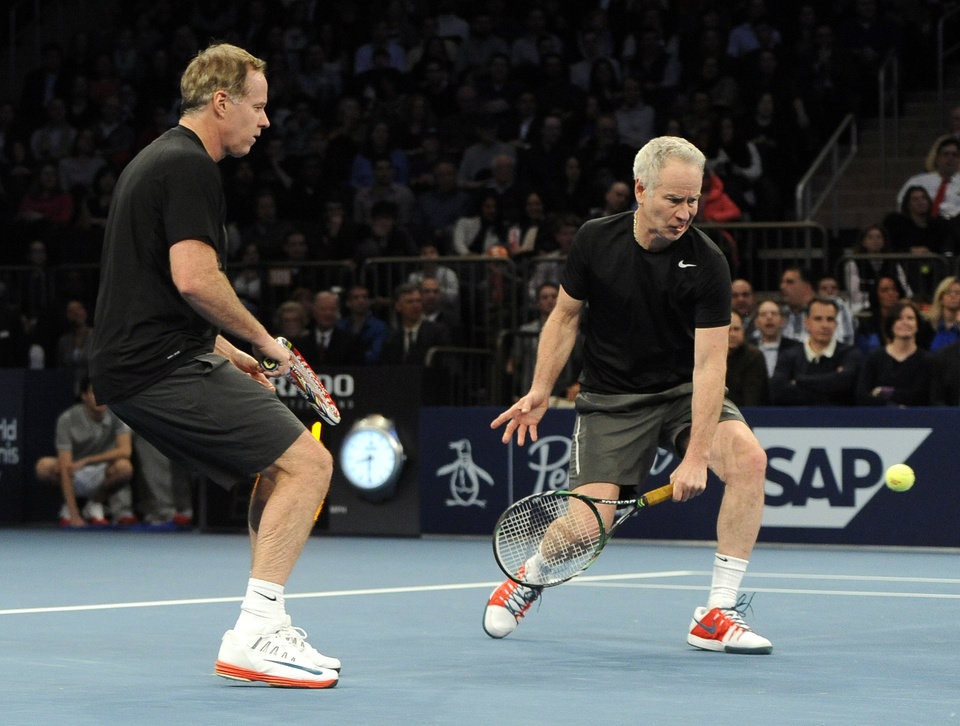 Photo - Patrick McEnroe, left, watches his brother John return a shot against Mike and Bob Bryan in the BNP Paribas Showdown Tennis Tournament on Monday, March 3, 2014, in New York. The Bryans won 8-3. (AP Photo/Kathy Kmonicek)