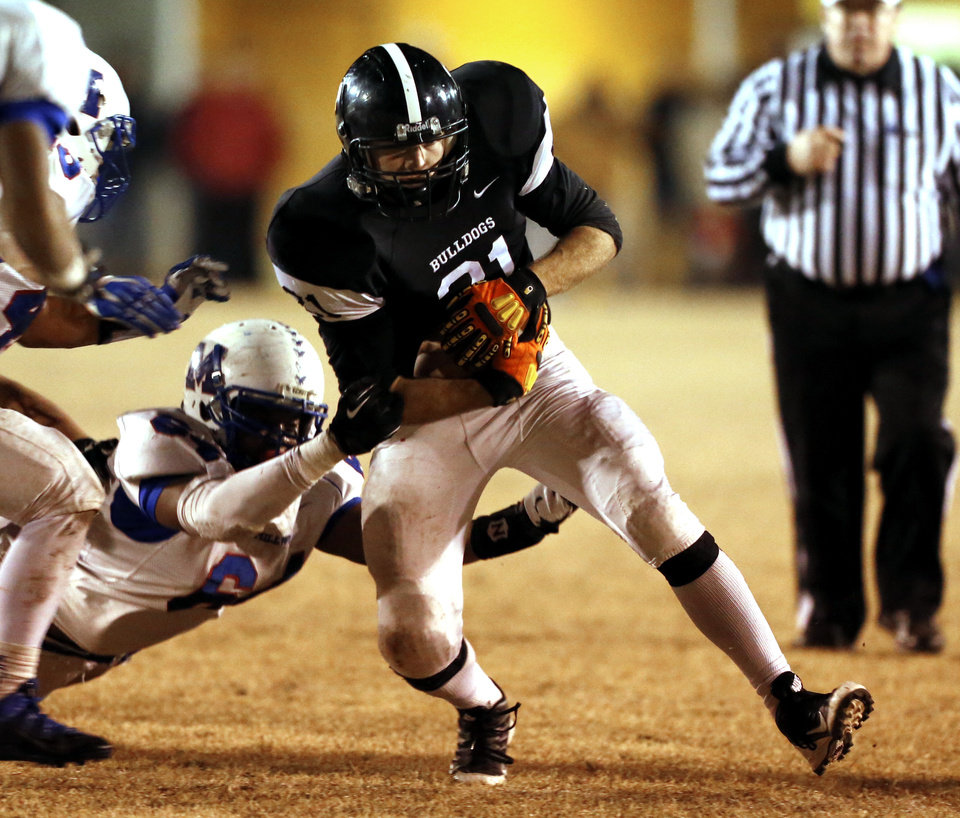 Photo - Meeker's Austin Watlington runs  and Kameron Lyons tries to take him down as the Millwood Falcons play the Meeker Bulldogs in state high school football playoffs on Friday, Nov. 29, 2013, in Meeker, Okla.  Photo by Steve Sisney, The Oklahoman