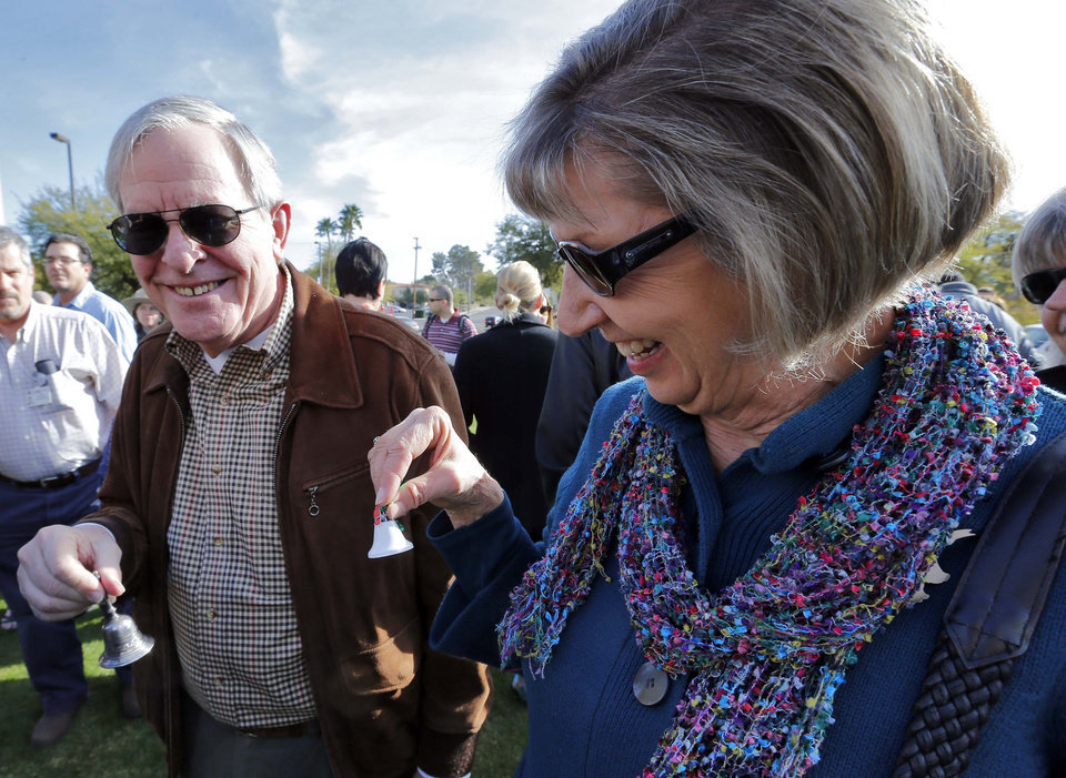 Photo - Tucson shooting survivor Pam Simon and her husband, Bruce Simon, ring bells during a remembrance ceremony on the third anniversary of the Tucson shootings, Wednesday, Jan. 8, 2014, in Tucson, Ariz. Six people were killed and 13 wounded, including U.S. Rep. Gabrielle Giffords, D-Ariz., in the shooting rampage at a community event hosted by Giffords in 2011.  Jared Lee Loughner was sentenced in November 2012 to seven consecutive life sentences, plus 140 years, after he pleaded guilty to 19 federal charges in the shooting. (AP Photo/Matt York)
