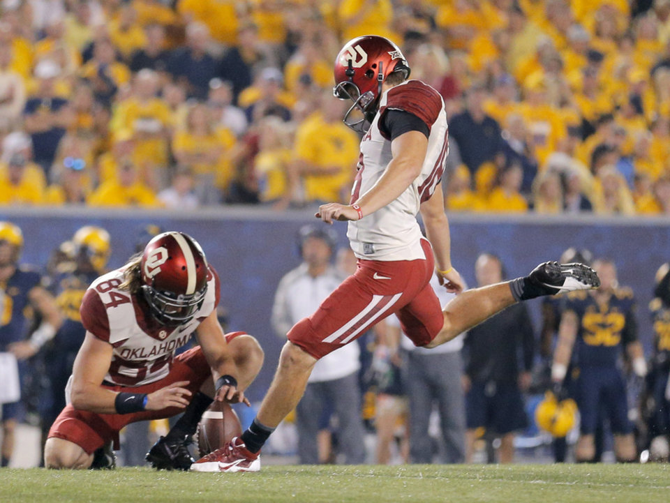 Photo - Oklahoma's Michael Hunnicutt (18) kicks a extra point in the third quarter to become OU's leading scorer during the college football game between West Virginia  Mountaineers and the University of Oklahoma Sooners at Milan Puskar Stadium in Morgantown, W.Va., Saturday, Sept. 20, 2014. Photo by Sarah Phipps, The Oklahoman