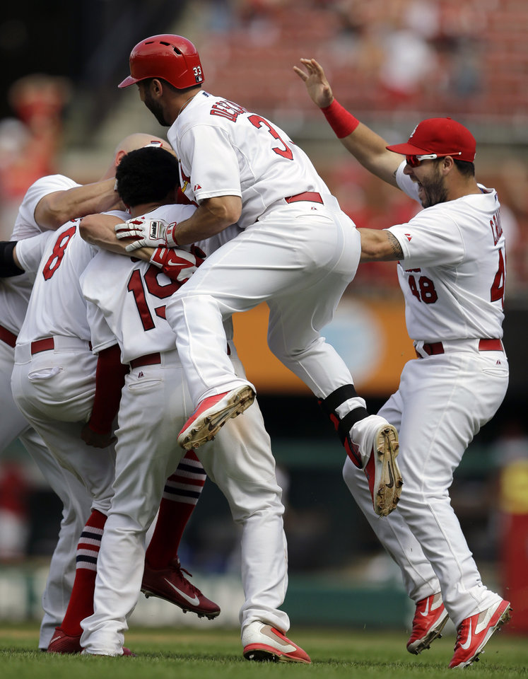 Photo - St. Louis Cardinals' Peter Bourjos (8) is congratulated by teammates after hitting a walkoff-single to score Yadier Molina during the ninth inning of a baseball game against the Pittsburgh Pirates, Wednesday, Sept. 3, 2014, in St. Louis. The Cardinals won 1-0. (AP Photo/Jeff Roberson)