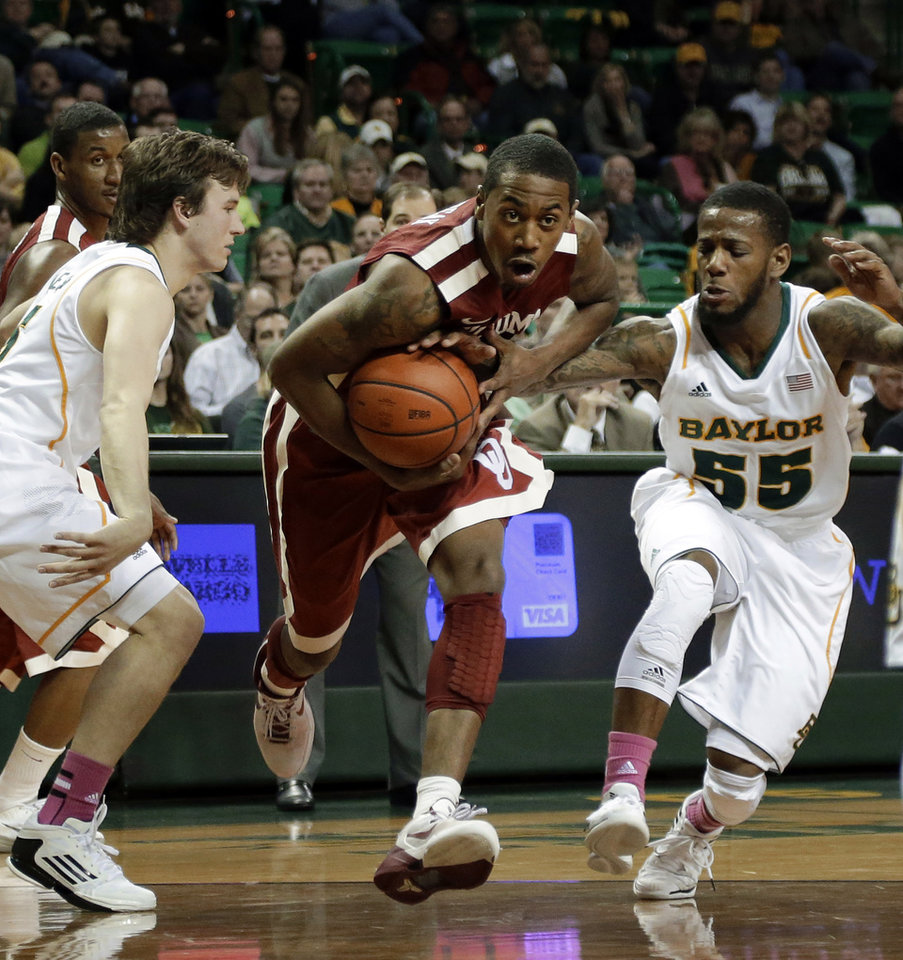 Baylor's Brady Heslip, left, and Pierre Jackson, defend as Oklahoma's Je'lon Hornbeak (5) finds an opening to the basket during the first half of an NCAA college basketball game Wednesday, Jan. 30, 2013, in Waco, Texas. (AP Photo/Tony Gutierrez)