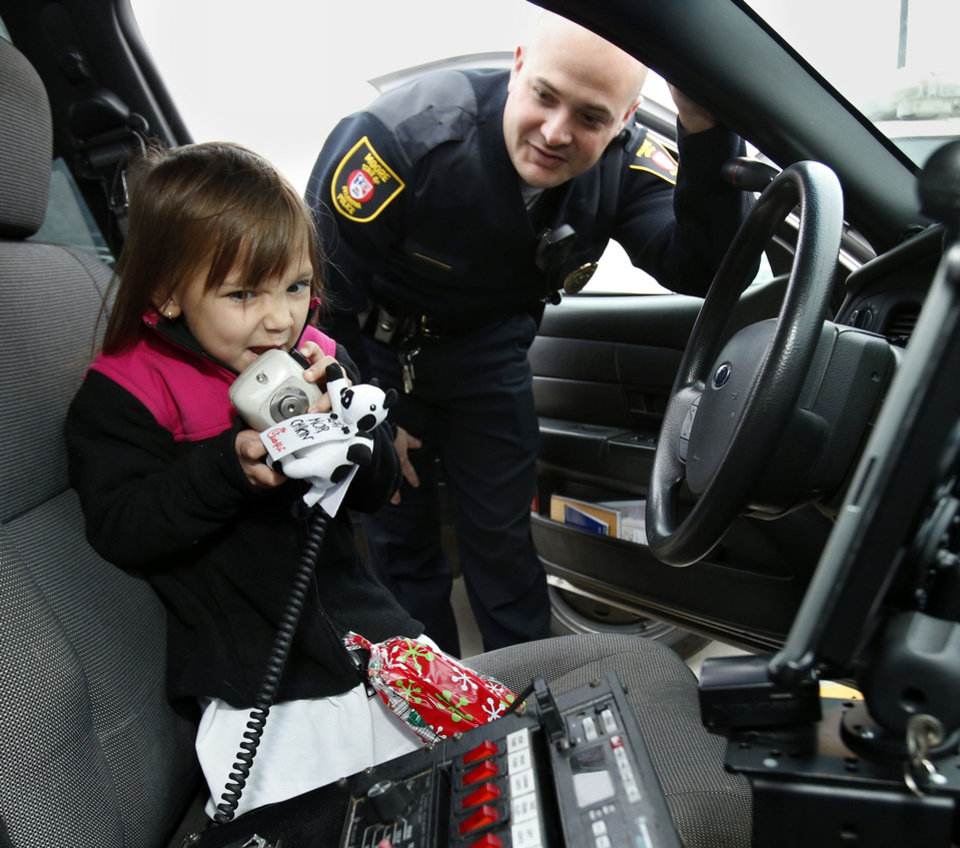 Kaelynn Fenimore, 5, uses the outside speaker of Moore police officer Trevor Troxell's police car.