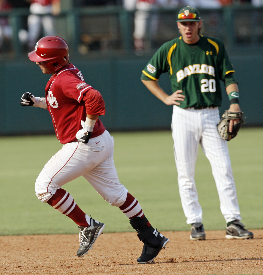 Photo - OU's Cody Reine (11) runs the bases past Baylor's Jake Miller (20) after hitting  a home run in the seventh inning during a Big 12 Baseball Championship tournament game between the Oklahoma Sooners and Baylor Bears at the Chickasaw Bricktown Ballpark in Oklahoma City,Thursday, May 24, 2012. OU won, 3-2. Photo by Nate Billings, The Oklahoman