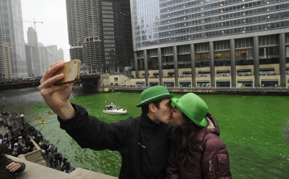 Photo - John Shepard and Gena Damento of Rochester Minn., take a photo of themselves kissing after the Chicago River was dyed green ahead of the St. Patrick's Day parade in Chicago, Saturday, March, 16, 2013.  With the holiday itself falling on a Sunday, many celebrations were scheduled instead for Saturday because of religious observances. (AP Photo/Paul Beaty)