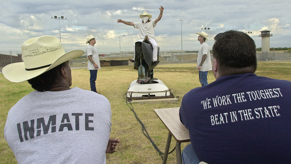 Photo - An Oklahoma State Penitentiary inmate tries to maintain his balance in 2006 while riding a mechanical bull at the prison in McAlester, while other inmates and a correctional officer, right, watch.  AP File Photo  KEVIN HARVISON -  AP
