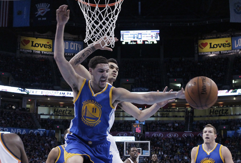 Photo - Golden State Warriors guard Klay Thompson (11) reaches for the ball in front of Oklahoma City Thunder's Steven Adams, rear, during the fourth quarter of an NBA basketball game in Oklahoma City, Friday, Jan. 16, 2015. Oklahoma City won 127-115. (AP Photo/Sue Ogrocki)
