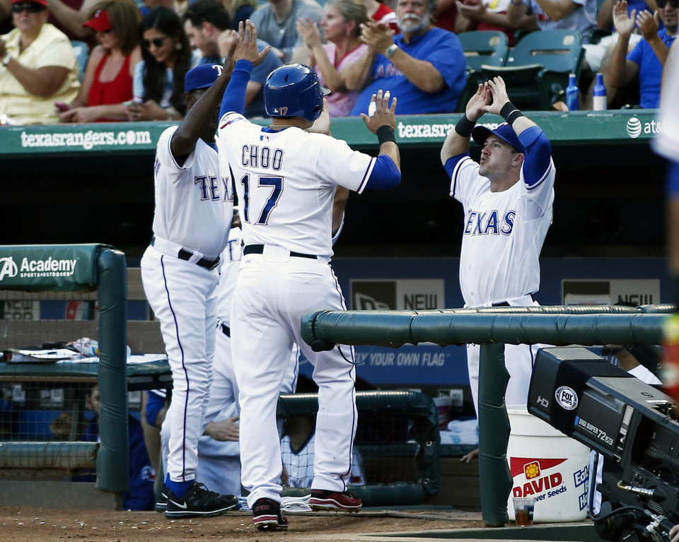 Photo - Texas Rangers' Shin-Soo Choo (17) is congratulated by manager Ron Washington, left, and Daniel Robertson, right, after scoring a run on a single hit by Adrian Beltre against the Los Angeles Angels during the first inning of a baseball game, Friday, Aug. 15, 2014, in Arlington, Texas. (AP Photo/Jim Cowsert)
