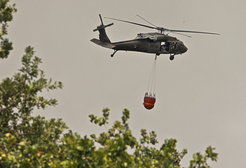 Photo - A helicopter brings water to the wildfire near Air Depot and Britton Rd.  on Tuesday, Aug. 30, 2011, in Oklahoma City, Okla. 