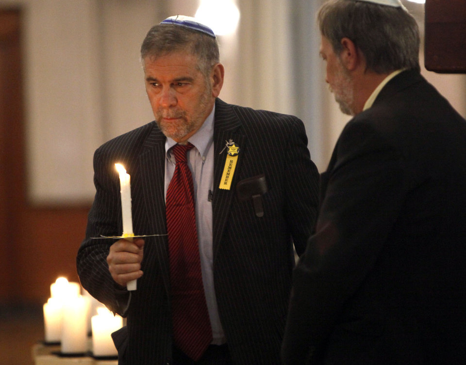Photo - Michael Berenbaum, Ph.D., prepares to light a candle during the 2012 Holocaust Commemoration service Tuesday at the Civic Center Music Hall in Oklahoma City. Berenbaum, of California, was the program's keynote speaker.  SARAH PHIPPS - SARAH PHIPPS