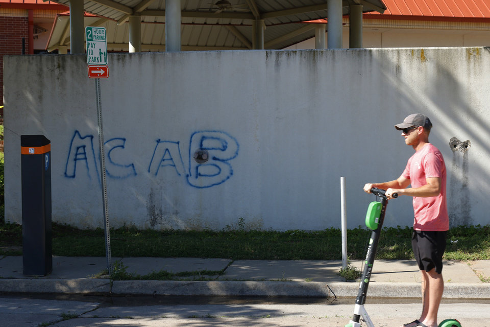 Photo - A man rides a scooter by graffiti on retaining wall at the Oklahoma County Jail. Damage from Saturday night protest in downtown Oklahoma City, Sunday, May 31, 2020. [Doug Hoke/The Oklahoman]
