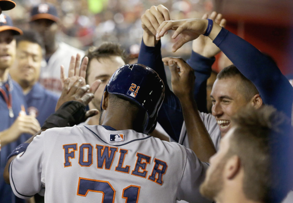 Photo - Houston Astros' Dexter Fowler, left, celebrates his run scored against the Arizona Diamondbacks with teammates, including George Springer, top right, during the second inning of a baseball game on Monday, June 9, 2014, in Phoenix. (AP Photo/Ross D. Franklin)