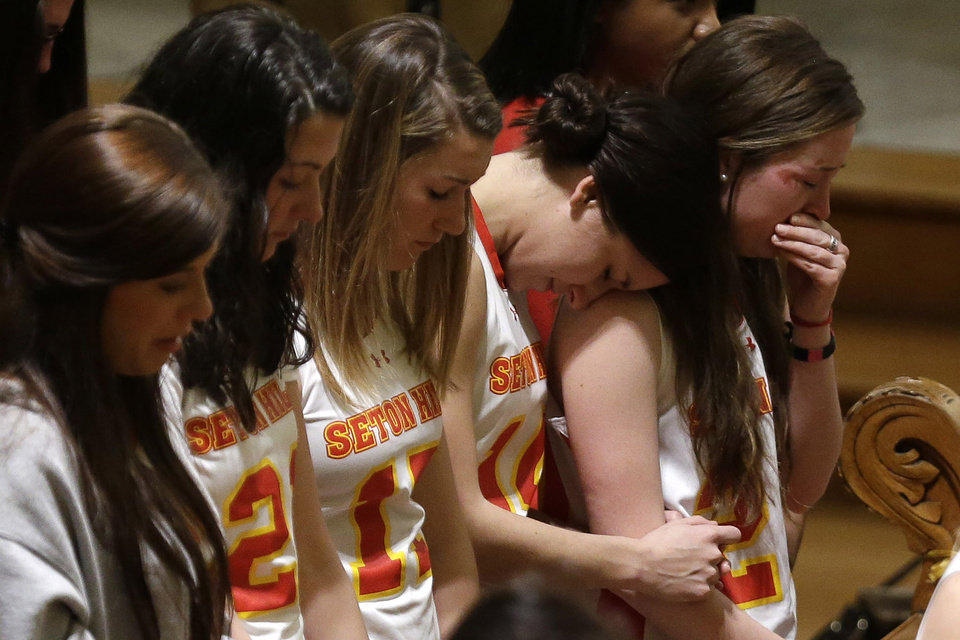 Photo - Members of the Seton Hill University's women's lacrosse team attend a memorial mass in St. Joseph Chapel on  the school's  Greensburg, Pa., campus Sunday, March 17, 2013. Women's lacrosse coach Kristina Quigley and the tour bus driver were killed when their tour bus carrying three coaches and members of the lacrosse team when the bus crashed at about 9 a.m., turnpike spokeswoman Renee Colborn said. It's not clear what caused the crash, but state police were investigating, said Megan Silverstram of the Cumberland County public safety department. (AP Photo/Gene J. Puskar)