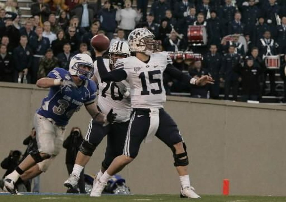 Photo - BYU quarterback Max Hall (15) is pursued by Air Force safety Chris Thomas (34) as BYU offensive lineman  Matt  Reynolds (70) tries to protect his quarterback in the fourth quarter of BYU's 38-24 win in an NCAA college football game at Air Force Academy, Colo., Saturday, Nov. 15, 2008. Hall threw for 354 yards and two touchdowns in the victory. (AP Photo/Justin Edmonds)