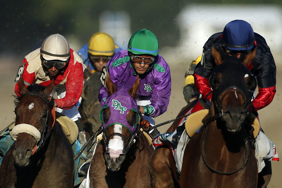 Photo - California Chrome, center, is flanked by Wicked Strong, left, and Tonalist, right, as they run down the backstretch during the 146th running of the Belmont Stakes horse race at Belmont Park, Saturday, June 7, 2014, in Elmont, N.Y.  Tonalist went on to win the race, denying California Chrome the Triple Crown victory. (AP Photo/Jason DeCrow)