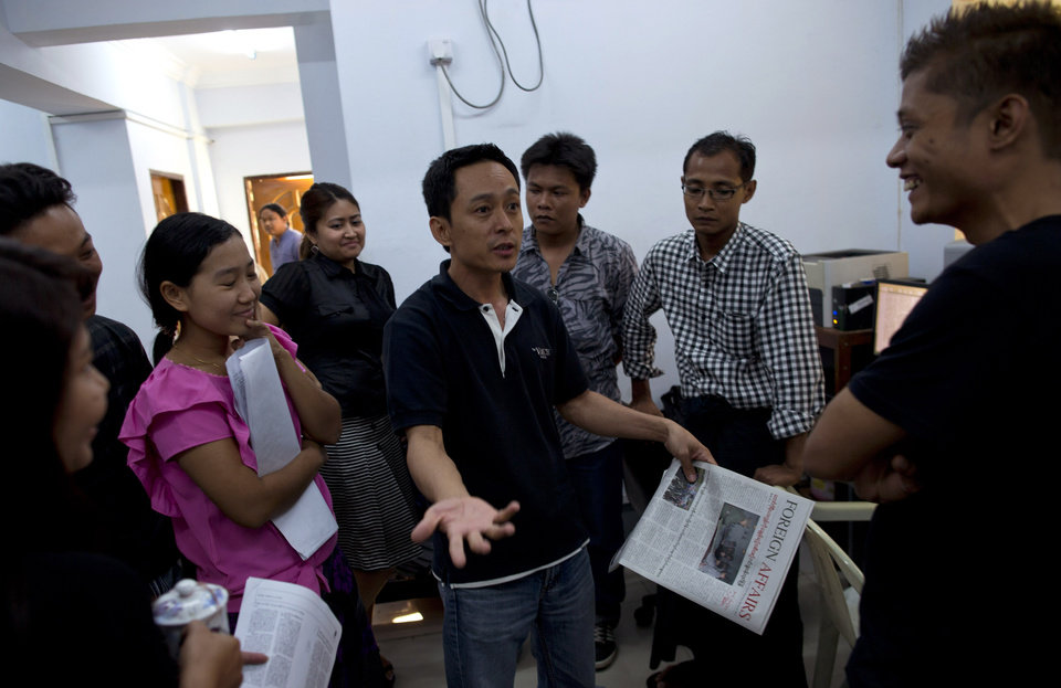 "In this March 14, 2013 photo, Kyaw Min Swe, center editor-in-chief of the weekly journal ""The Voice,"" gestures during a discussion with his colleagues in newsroom, Yangon, Myanmar.  Myanmar's newly energized press corps is calling on the government to revise a proposed new publishing law, saying it will mark a severe setback to press freedoms and replace the country's old censorship regime with other forms of repression. Kyaw Min Swe, editor-in-chief of the private weekly The Voice, said the speaker of Parliament's lower house did not allow debate on the legislation ""because many media organizations have sent letters of criticism"" to parliamentary officials. Legislators were in session until Monday evening and were not immediately available. (AP Photo/Gemunu Amarasinghe)"