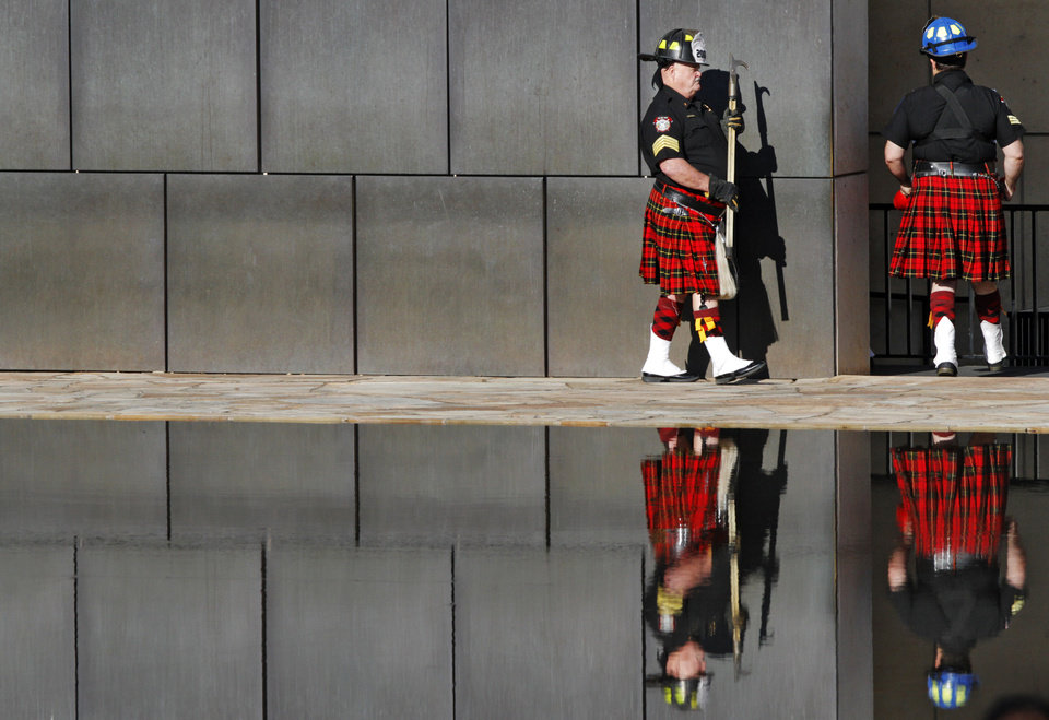 Photo -  Members of the Oklahoma Fire Pipes and Drums walk through one of the Gates of Time at the 19th anniversary Remembrance Ceremony at the Oklahoma City National Memorial Saturday morning, April 19, 2014, to honor the memory of the 168 victims killed in the 1995 bombing of the Murrah Federal Building. Photo by KT King, The Oklahoman