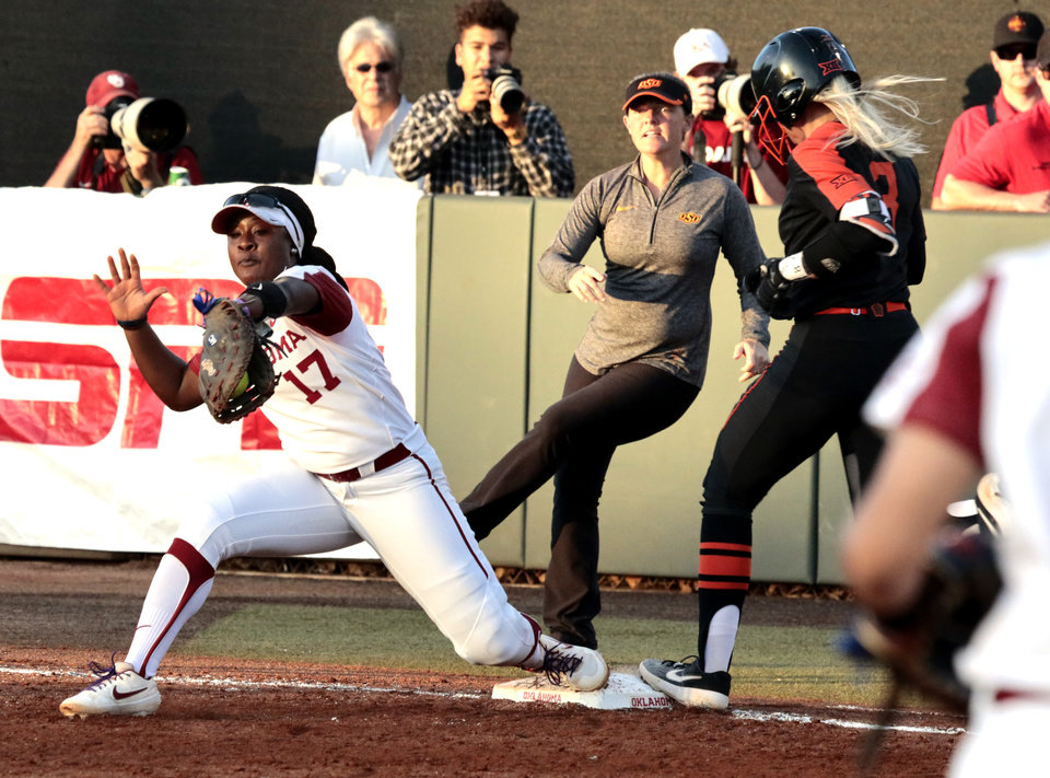 Photo - Sooner first baseman Shay Knighten retrieves a wide throw from catcher Lynnsie Elam to put out Samantha Show in Bedlam softball as the University of Oklahoma Sooners (OU) play the Oklahoma State Cowboys (OSU) at Marita Hynes Field at the OU Softball Complex on  May 4, 2019 in Norman, Okla.  [Steve Sisney/For The Oklahoman]