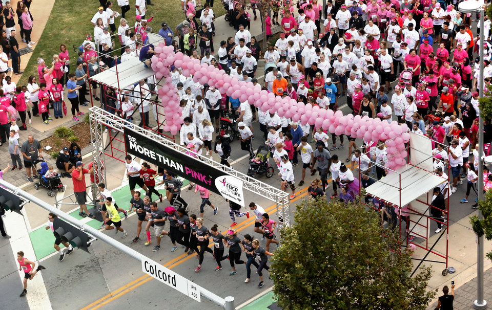 Photo -  A mass of participants walk or jog in the fun run during the Susan G. Komen Race for the Cure on Saturday in downtown Oklahoma City. [PHOTO BY STEVE SISNEY, THE OKLAHOMAN]