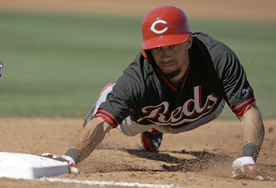 Photo - Cincinnati Reds' Billy Hamilton dives back to first base during the fourth inning of a spring exhibition baseball game against the Texas Rangers Monday, March 10, 2014, in Suprise, Ariz. (AP Photo/Darron Cummings)