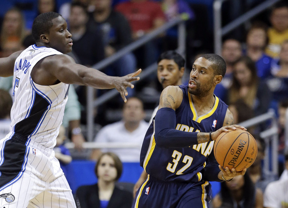 Photo - Indiana Pacers' C.J. Watson (32) looks to pass the ball around Orlando Magic's Victor Oladipo, left, during the first half of an NBA basketball game in Orlando, Fla., Sunday, Feb. 9, 2014. (AP Photo/John Raoux)