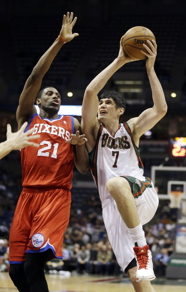 Photo - Milwaukee Bucks' Ersan Ilyasova (7) drives against Philadelphia 76ers' Thaddeus Young (21) during the second half of an NBA basketball game, Tuesday, Jan. 22, 2013, in Milwaukee. (AP Photo/Jeffrey Phelps)