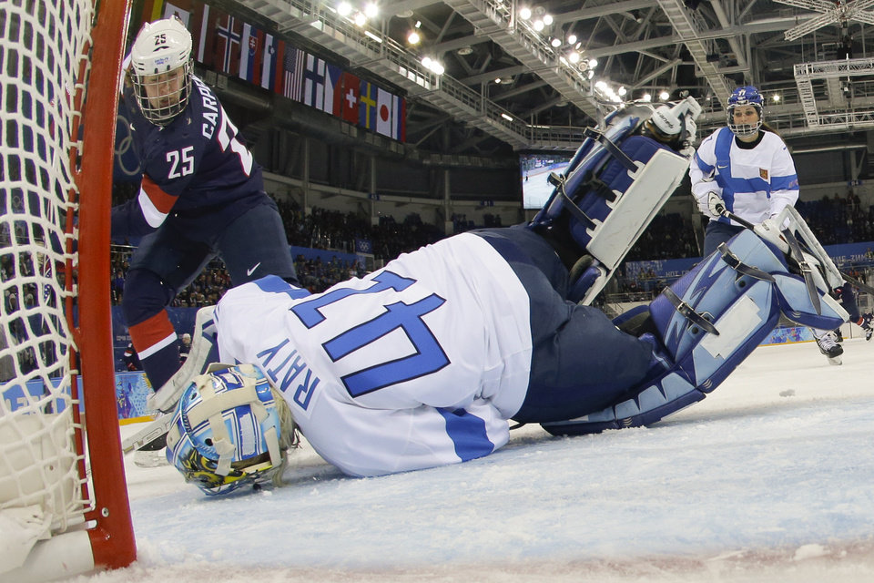 Photo - Goalkeeper Noora Raty of Finland falls on the puck to block a who by Alex Carpenter of the Untied States during the third period of the 2014 Winter Olympics women's ice hockey game at Shayba Arena, Saturday, Feb. 8, 2014, in Sochi, Russia. (AP Photo/Matt Slocum)