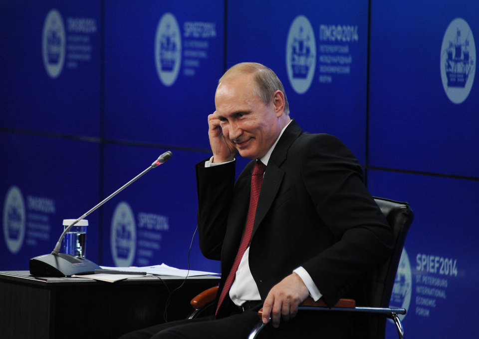 """Photo - Russian President Vladimir Putin listens during the St.Petersburg International Investment Forum in St Petersburg, Russia, Friday, May 23, 2014. Speaking at the investment forum, Putin blamed the West for encouraging a """"coup"""" in Ukraine, when the nation's pro-Russian president was chased from power after months of protests. He said that Ukraine is now facing """"chaos and a full-scale civil war.""""  (AP Photo/RIA Novosti Kremlin, Mikhail Klimentyev, Presidential Press Service)"""
