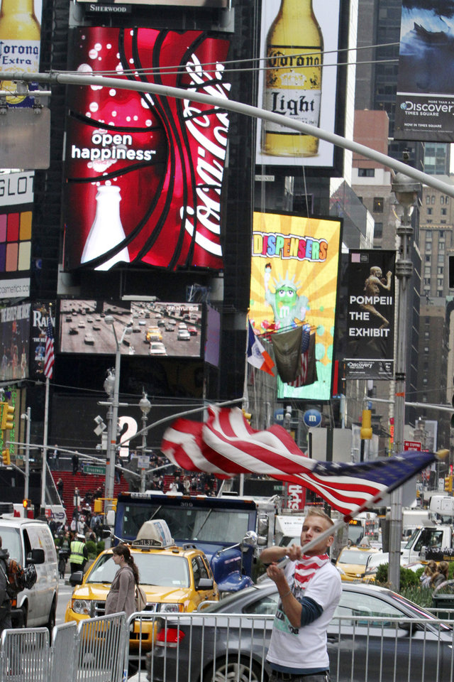 Photo - Colin Marshal, of Little Falls, N.J. waves an American flag in New York's Times Square,  Monday, May 2, 2011.  President Barack Obama announced Sunday night that Osama bin Laden was killed in an operation led by the United States.  (AP Photo/Mary Altaffer) ORG XMIT: NYMA105