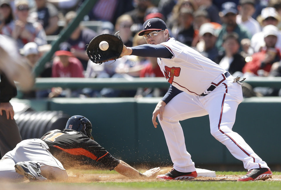 Photo - Miami Marlins' Christian Yelich dives back to first as Atlanta Braves first baseman Freddie Freeman waits on the pick-off attempt during the fifth inning of an exhibition baseball game in Kissimmee, Fla., Wednesday, March 26, 2014. (AP Photo/Carlos Osorio)