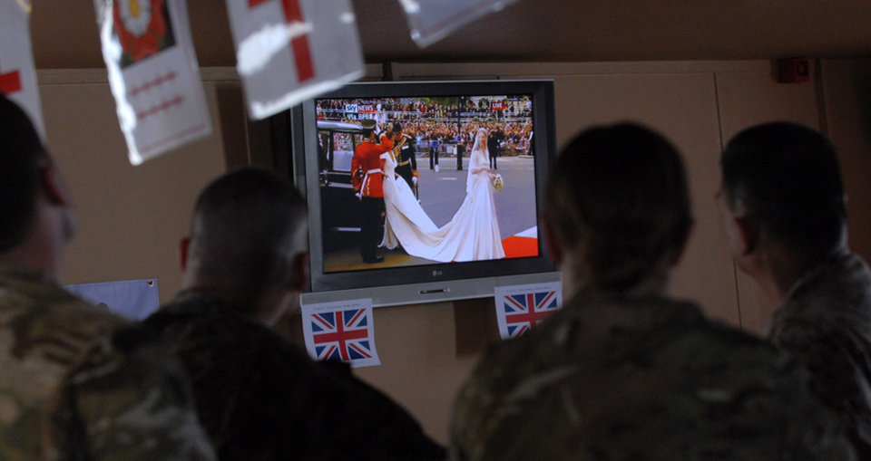 Photo - In this photo provided by International Security Assistance Force Regional Command (South), service members watch the Royal Wedding of Prince William and Kate Middleton, Friday, April 29, 2011, while taking a break at a coffee house on Kandahar Airfield in Kandahar, Afghanistan. (AP Photo/US Navy - Ensign Haraz N. Ghanbari)  ORG XMIT: AFGH107