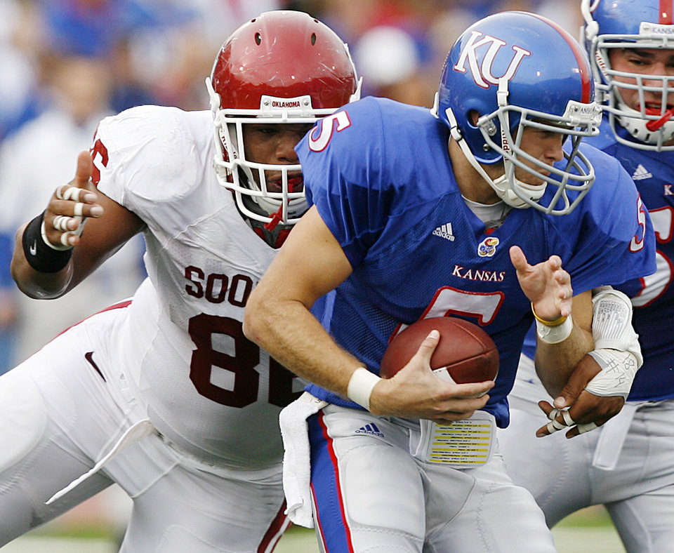 Photo - Oklahoma's Adrian Taylor (86) sacks Kansas quarterback Todd Reesing (5) during the first half of the college football game between the University of Oklahoma Sooners (OU) and the University of Kansas Jayhawks (KU) on Saturday, Oct. 24, 2009, in Lawrence, Kan. Photo by Chris Landsberger, The Oklahoman