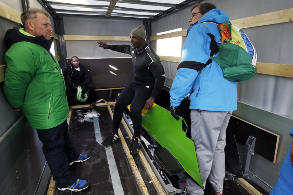 Photo - Winston Watts, the driver for JAM-1 from Jamaica, center, speaks to coaches and support staff as his brakeman Wayne Blackwood watches from the back of the equipment truck after a training run for the two-man bobsled at the 2014 Winter Olympics, Thursday, Feb. 6, 2014, in Krasnaya Polyana, Russia. (AP Photo/Natacha Pisarenko)