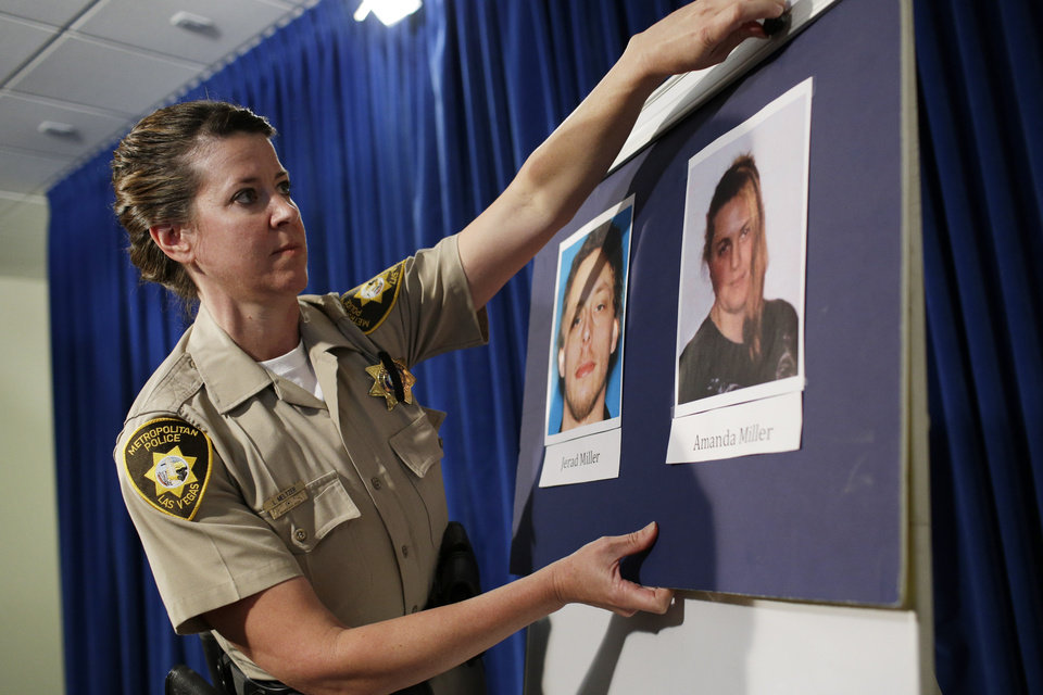 Photo - Las Vegas Metropolitan Police Department Officer Laura Meltzer hangs up pictures of suspects Jerad Miller and Amanda Miller before a news conference Monday, June 9, 2014 in Las Vegas. Two police officers were having lunch at a strip mall pizza buffet when the Millers fatally shot them in a point-blank ambush, then fled to a nearby Wal-Mart where they killed a third person and then themselves in an apparent suicide pact, authorities said. (AP Photo/John Locher)