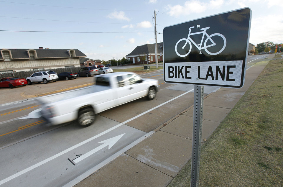 Photo - A pickup drives past Edmond's first bike lane along University Drive that officially opened on Sunday with an Open Streets celebration. PHOTO BY PAUL HELLSTERN, THE OKLAHOMAN.  PAUL HELLSTERN - OKLAHOMAN