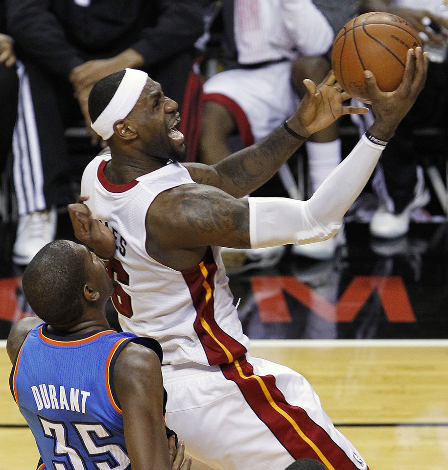 Photo - Miami Heat small forward LeBron James (6) is fouled by Oklahoma City Thunder small forward Kevin Durant (35) during the first half at Game 3 of the NBA Finals basketball series, Sunday, June 17, 2012, in Miami. James made the basket. (AP Photo/Wilfredo Lee)  ORG XMIT: NBA122