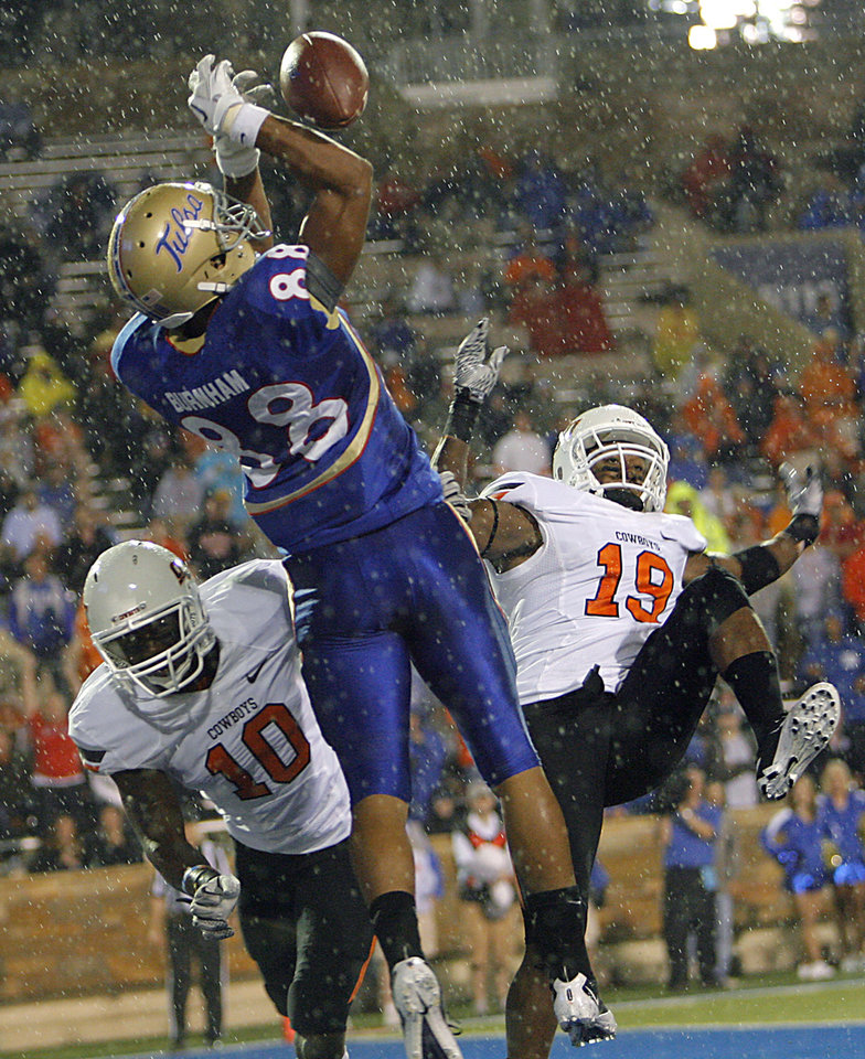 Photo - Oklahoma State's Markelle Martin (10) and Brodrick Brown (19) break up a pass for Tulsa's Bryan Burnham (88) during a college football game between the Oklahoma State University Cowboys and the University of Tulsa Golden Hurricane at H.A. Chapman Stadium in Tulsa, Okla., Sunday, Sept. 18, 2011. Photo by Chris Landsberger, The Oklahoman