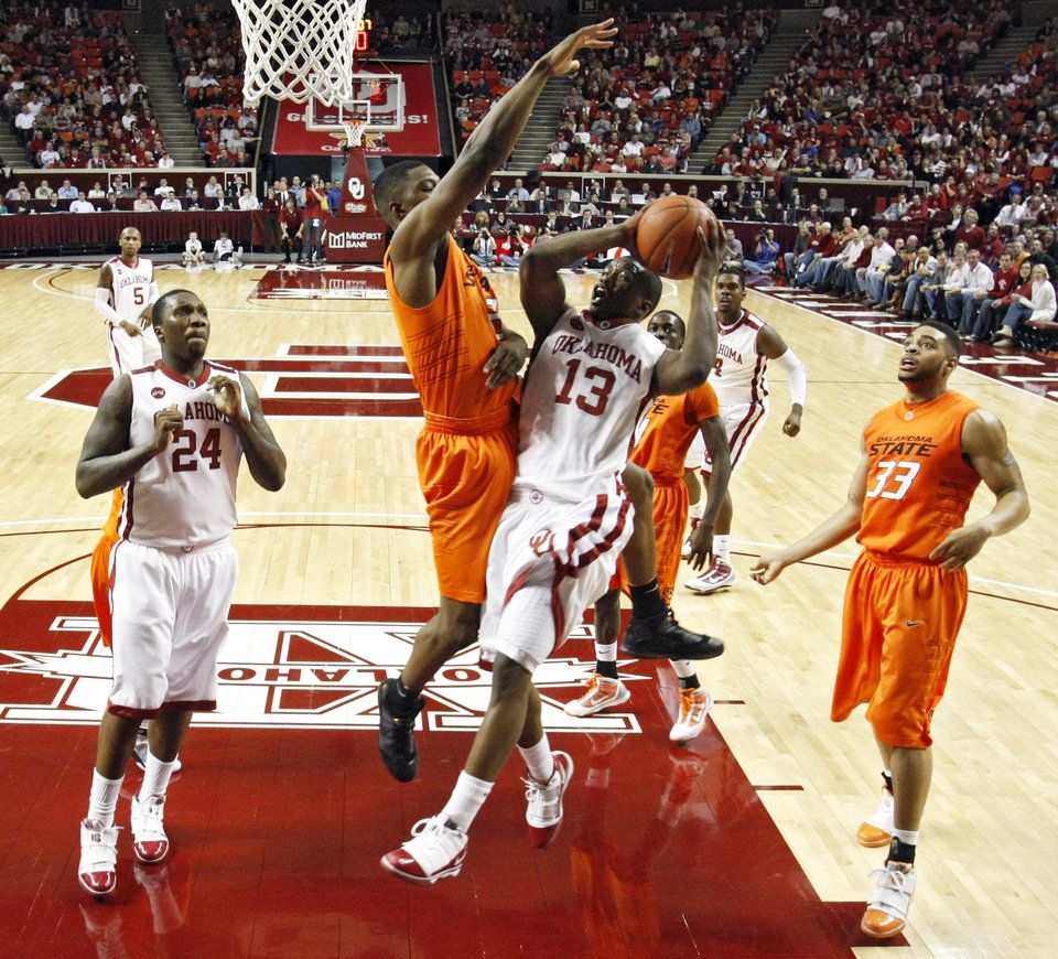 Photo - OU's Willie Warren (13) is fouled by OSU's Obi Muonelo (2) as he drives to the basket during the first half of the college bedlam basketball game between The University of Oklahoma Sooners (OU) and Oklahoma State University University Cowboys (OSU) at the Lloyd Noble Center on Monday, Jan. 11, 2010, in Norman, Okla.
