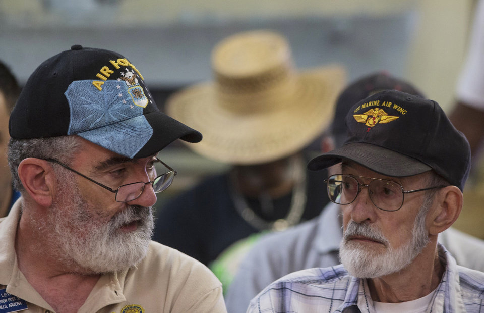 Photo - Vietnam veteran Gene Stoesser, right, talks with Veterans Crisis Command Center volunteer Chuck Lewis, left, while he waits for an appointment Tuesday, June 10, 2014, at American Legion Post 1 in Phoenix. Stoesser was told on May 2, 2014, that he needs heart surgery. The American Legion has set up a crisis center in Phoenix to help veterans get medical care in a first-of-its-kind event in the American Legion's nearly 100-year history.(AP Photo/The Arizona Republic, Mark Henle) MESA OUT  MARICOPA COUNTY OUT  MAGS OUT  NO SALES