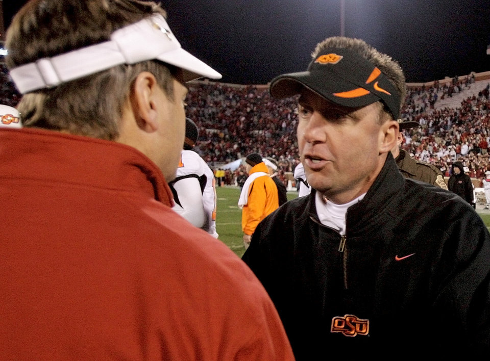 Photo - OU head coach Bob Stoops, left, and OSU head coach Mike Gundy talk after the college football game between the University of Oklahoma Sooners (OU) and the Oklahoma State University Cowboys (OSU) at the Gaylord Family-Memorial Stadium on Saturday, Nov. 24, 2007, in Norman, Okla. 