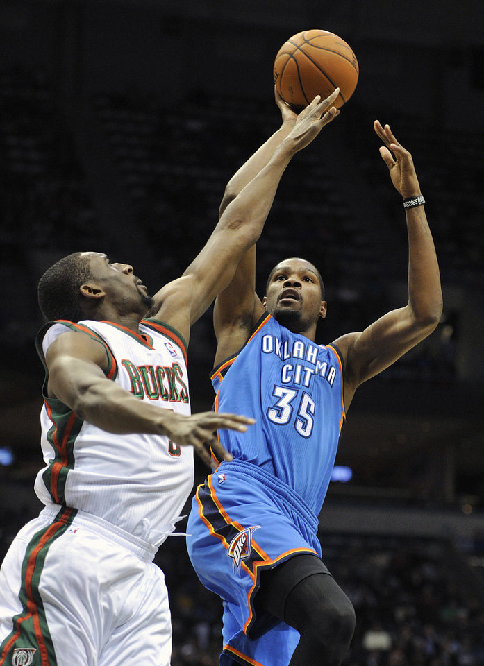 Photo - Milwaukee Bucks' Ekpe Udoh left, tries to block the shot of the Oklahoma City Thunder's Kevin Durant (35) during the first half of an NBA basketball game Saturday, Nov. 16, 2013, in Milwaukee. (AP Photo/Jim Prisching)