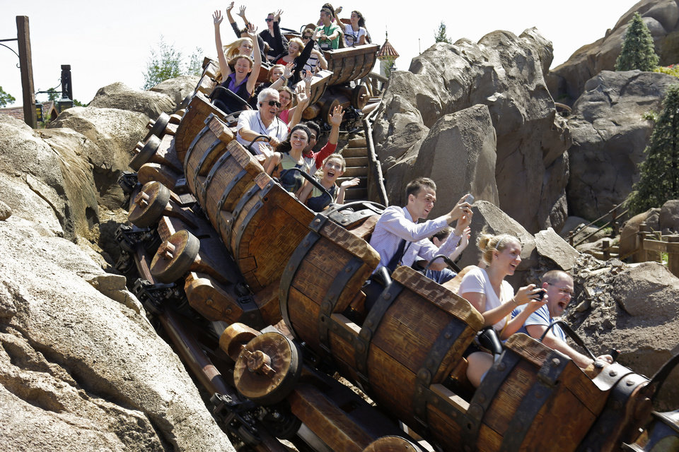 Photo - This May 16, 2014 photo shows Disney castmembers testing the new Seven Dwarfs Mine Train roller coaster in the Magic Kingdom at Walt Disney World, in Lake Buena Vista, Fla. The ride will be open to park guests on May 28. (AP Photo/John Raoux)