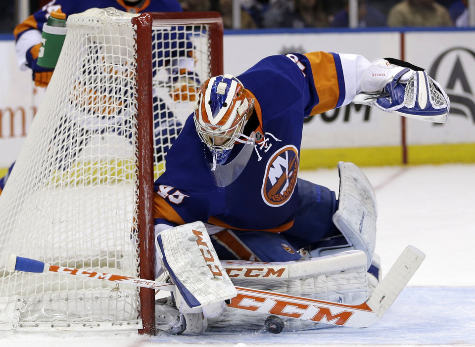 Photo - New York Islanders goalie Anders Nilsson makes a save during the first period of the NHL hockey game against the Minnesota Wild, Tuesday, March 18, 2014, in Uniondale, New York. (AP Photo/Seth Wenig)