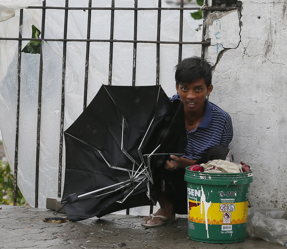 Photo - A resident holding a broken umbrella seeks shelter by a concrete wall under a slight rain and wind brought by Typhoon Koppu Sunday, Oct.18, 2015 in Manila, Philippines. The slow-moving typhoon blew ashore with fierce wind in the northeastern Philippines early Sunday, toppling trees and knocking out power and communications. Officials said there were no immediate reports of casualties. (AP Photo/Bullit Marquez)