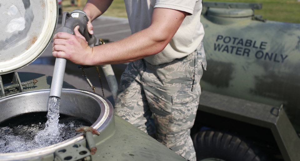 Photo - Ohio Air National Guard Senior Airman Nick Wander fills a 400 gallon military water buffalo with fresh drinking water, Sunday, Aug. 3, 2014, at Woodward High School in Toledo, Ohio. More tests are needed to ensure that toxins are out of Toledo's water supply, the mayor said Sunday, instructing the 400,000 people in the region to avoid drinking tap water for a second day. Toledo officials issued the warning early Saturday after tests at one treatment plant showed two sample readings for microsystin above the standard for consumption, possibly because of algae on Lake Erie. (AP Photo/Haraz N. Ghanbari)
