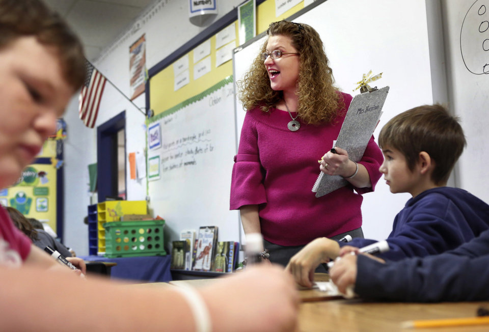 Photo - Sallie Harrison teaches a lesson in long division to her fourth-grade students. Harrison has has multiple sclerosis.    Photo by Jim Beckel, The Oklahoman  Jim Beckel - THE OKLAHOMAN
